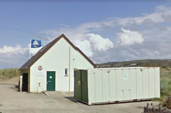 The toilet block at Poppit Sands with the Blue Flag flying behind it