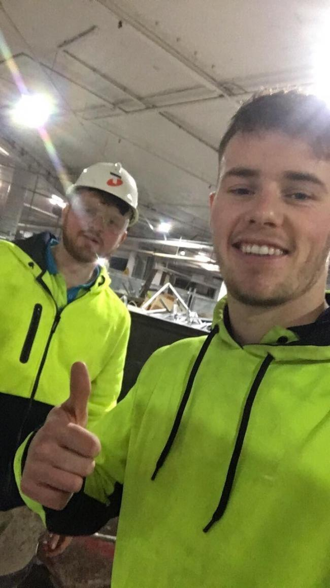 Have-a-go heroes Joe Davies (left) and Davy Lewis are pictured back on their labouring shift at Melbourne shopping centre after apprehending a fleeing supermarket thief
