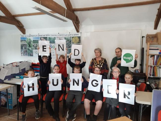 Cardigan mayor Cllr Shan Williams and town foodbank manager Alan Faunch with pupils from Ysgol Gynradd Aberteifi highlighting End Hunger Awareness Week