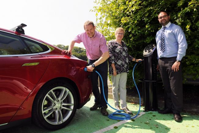 William Silverstone (left) charging his car at the Mart car park in Newcastle Emlyn with Cllr Hazel Evans and Thomas Evans, transport planner