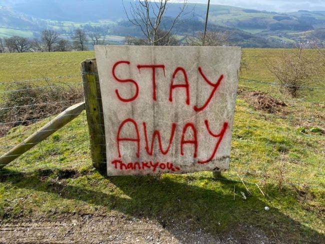 A Llangollen resident has erected a makeshift banner near Dinas Bran Castle urging tourists to stay away from the area.