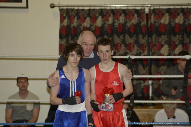Tivyside Advertiser: TABLES TURNED: Cardigan boxer Emyr Simmons (red shirt) is pictured with Bridgend opponent Bradley Pearce and Cardigan ABC president Chris Lawson. Photo courtesy of www.storm-development.co.uk