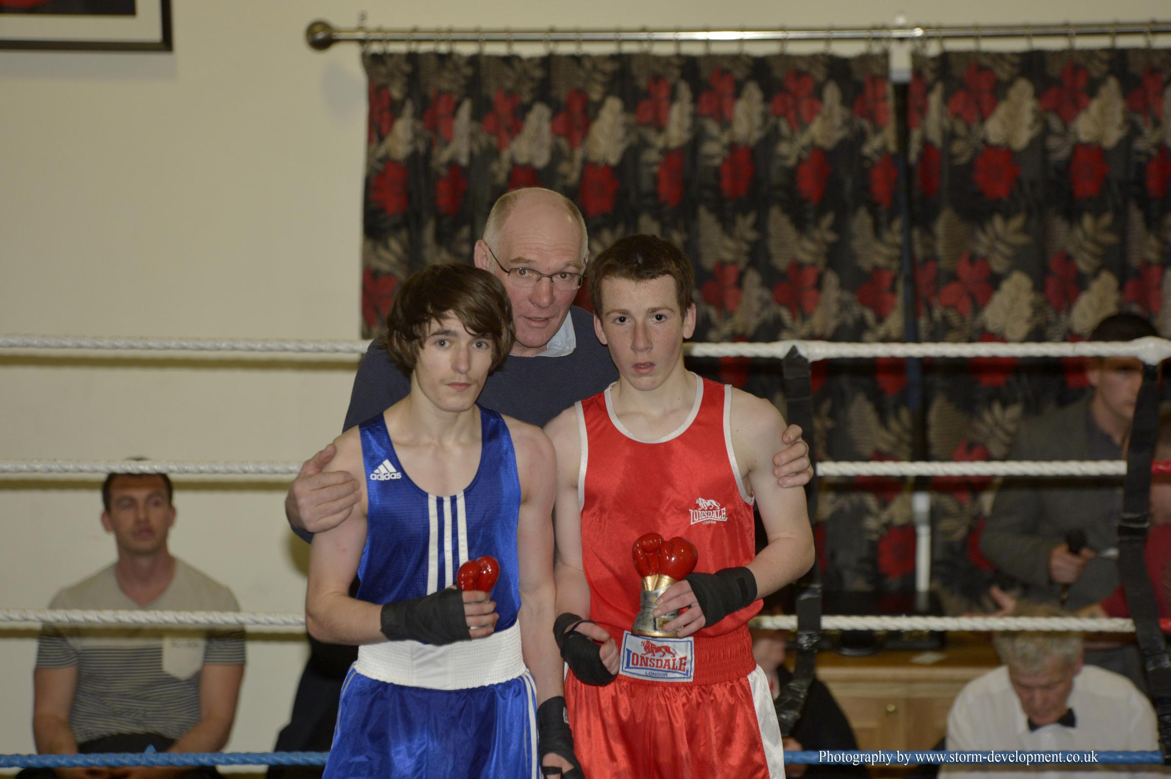TABLES TURNED: Cardigan boxer Emyr Simmons (red shirt) is pictured with Bridgend opponent Bradley Pearce and Cardigan ABC president Chris Lawson. Photo courtesy of www.storm-development.co.uk