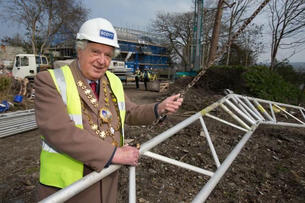 Cardigan mayor Cllr Gwynfi Jenkins with one of the giant steel struts that has been covering Castle Green House