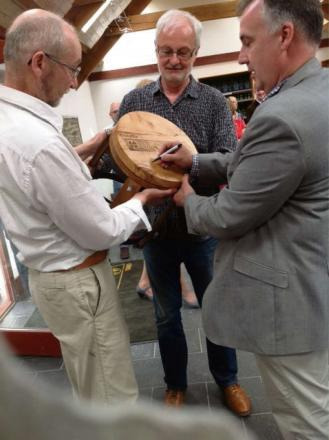 MP Mark Williams signs a stool with John Savage Onstwedder and Peter Jackson of the Ceredigion Arts Trail