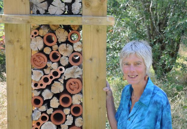 "Sculptor Wendy Earle with ""Shelf Life"" an upright stack of shale, oak, clay pipes and slates topped off by four bronze roundhouses for birds and bats. (8818188)"