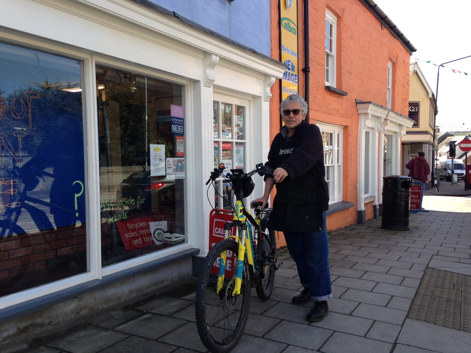 Tom Wells reunited with his stolen bike outside his cycle shop in Cardigan