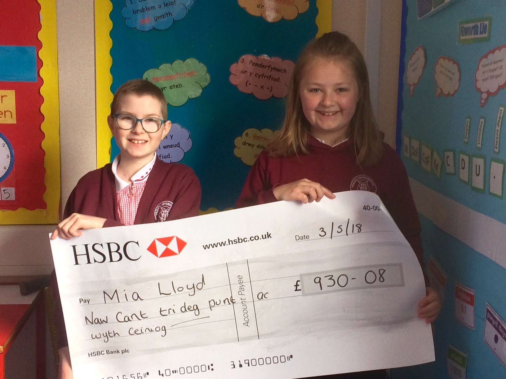 Cari Davies hands over a cheque to schoolfriend Mia Lloyd
