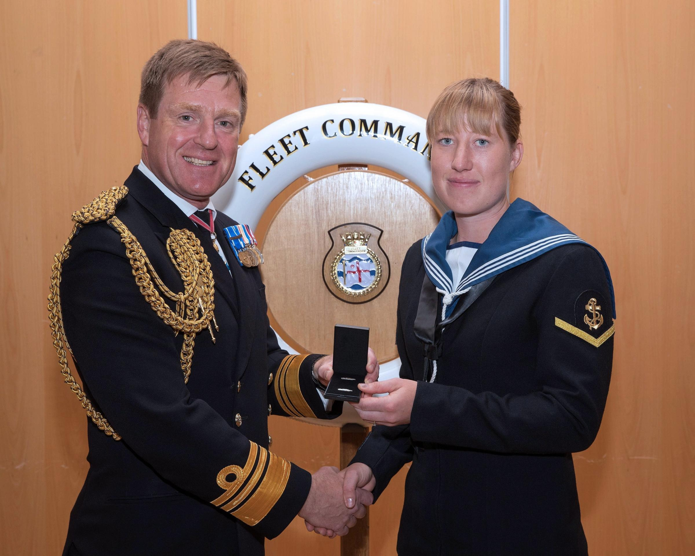 Vice-admiral Ben Key presents Sarah Griffiths with her Queen's Commendation at Portsmouth