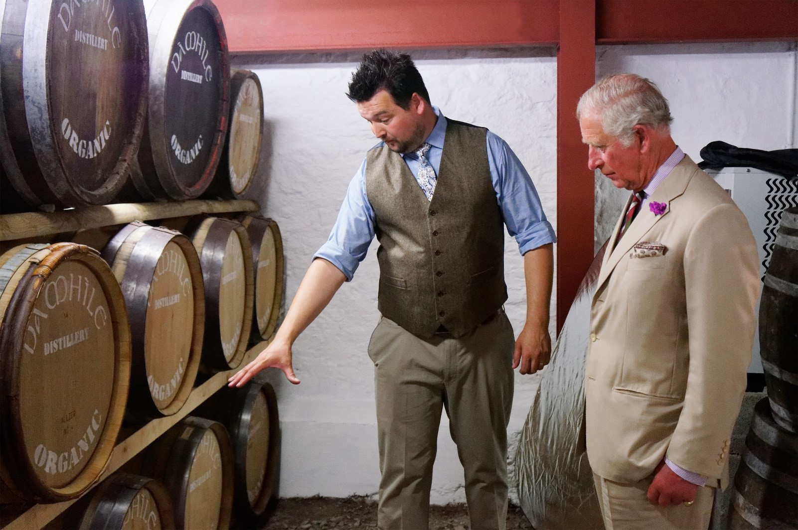 John-James Savage-Onstwedder showing Prince Charles the various casks of organic Welsh whisky in the bonded warehouse at Da Mhile Distillery, Llandysul