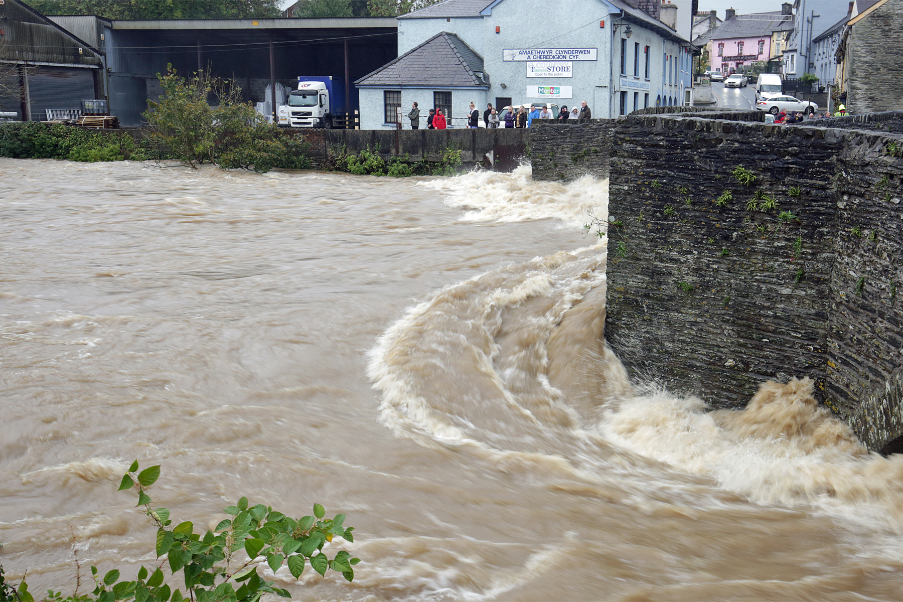 Onlookers watch as the River Teifi batters the town bridge in Newcastle Emlyn during Storm Callum. PICTURE: Barry Adams