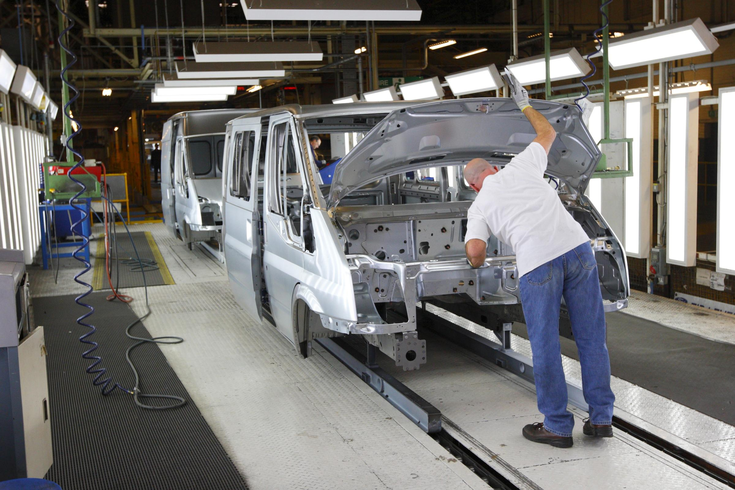 Ford workers check the bodywork of Transit vans