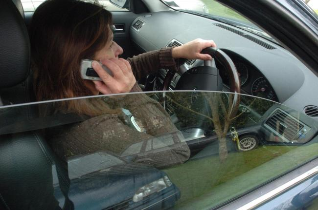 Posed picture of a driver using a mobile phone. PICTURE: Barry Batchelor/PA Wire