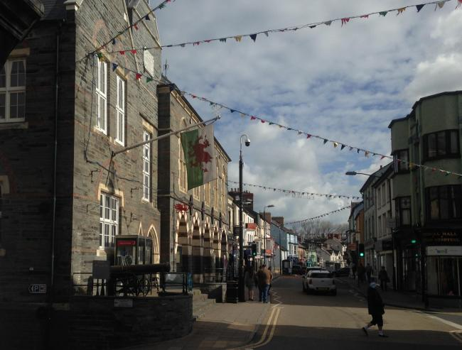 The Welsh flag hanging from the Guildhall in Cardigan which is obscuring the police CCTV camera behind it