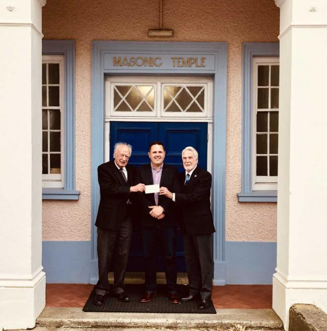 The Worshipful Master, W. Bro John Stark, together with W. Bro Bryn Barton the Charity Steward of Strumble Lodge, present a cheque awarded by the West Wales Provincial Grand Charity for £2,500 to Matthew Jenkins, Musical Director of Goodwick Brass B